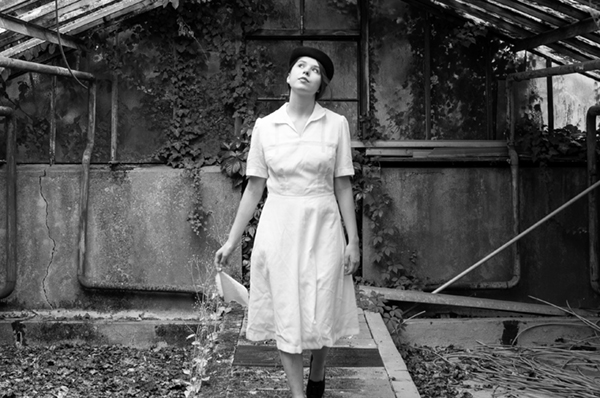 Das Taschentuch im Film - eine junge Frau im Stil der 1940er Jahre ist verträumt mit ihrem Taschentuch in einem Gewächshaus spazieren