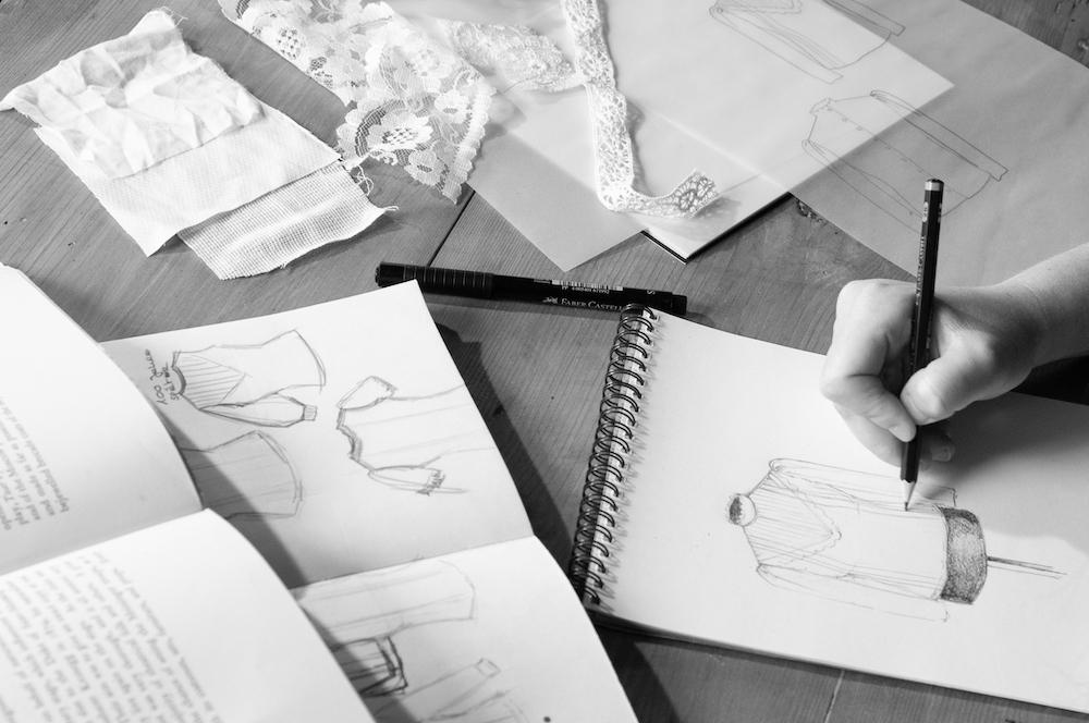 Ein typischer Arbeitsplatz: ein Kostümbildner zeichnet eine Bluse auf einen Skizzenblock, Stoffmuster, weitere Skizzen und ein Buch über Kostümgeschichte am Schreibtisch