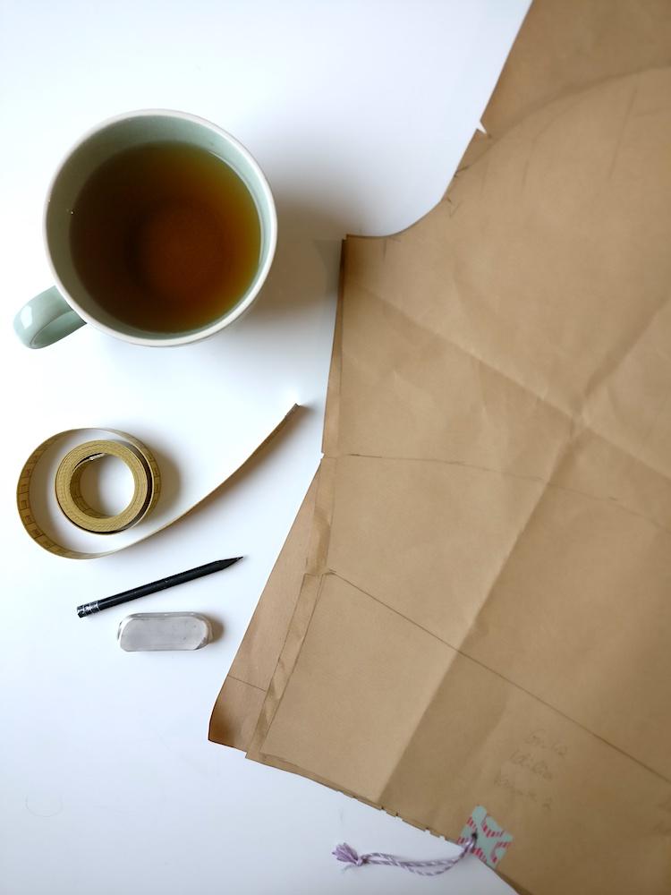 Ein typischer Schreibtisch vom Gewandmeister: Selbst gezeichnetes Schnittmuster, Maßband, Bleistift, Radiergummi und eine Tasse Tee