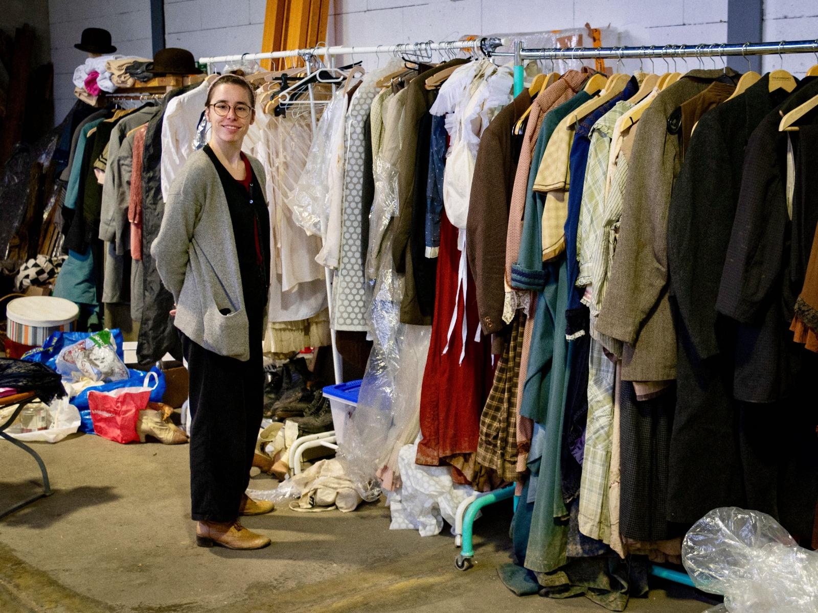 Eine Kostümbildnerin steht vor der gesamten Kostümen für einen historischen Spielfilm